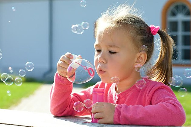 Cute little girl is blowing soap bubbles while sitting at table outdoors
